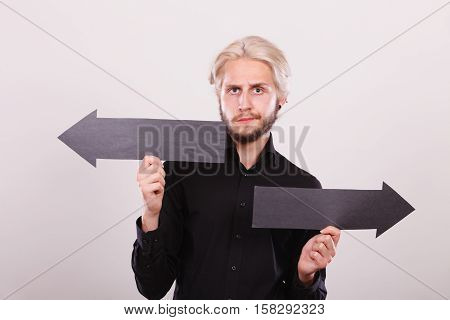 Planning directions choices concept. Man holding black arrow pointing left and right opposite directions. Indoor shot on light background