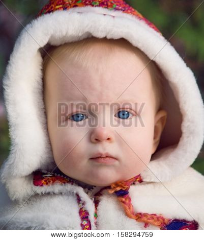 Close-up portrait of a serious cute baby girl in a white and red fur coat on a sunny winter day.