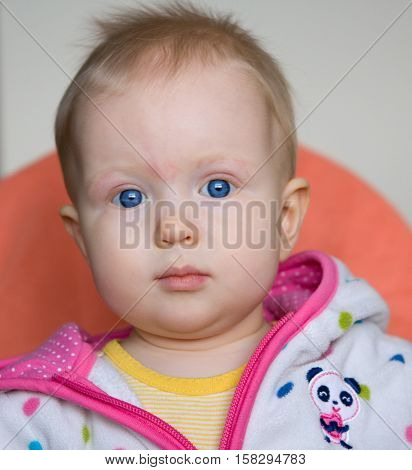 Cute blond baby girl with blue eyes on a white and orange background.