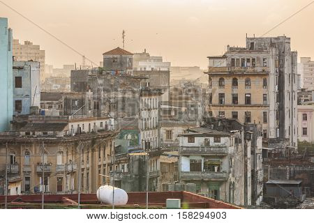 great dramatic view of old, retro antique Havana Cuban town, staying in dusty smog environment and overcast sky with people in background