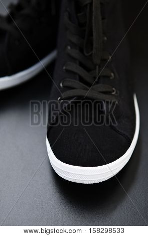Black keds sneakers with black laces and white rubber sole foot on black background closeup