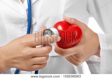 Young female cardiologist holding plastic heart, close up