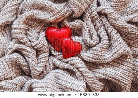 Closeup macro texture of knitted wool fabric material with red candy hearts on top clothing background with wrinkles and folds Valentine holiday card love concept