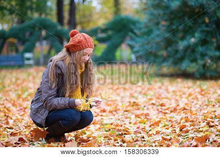 Girl Gathering Leaves On A Fall Day