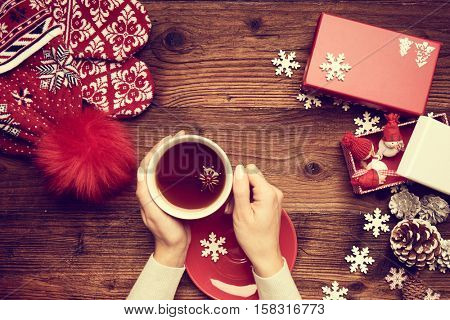 Set of colorful Christmas gifts lying on a table with black background and female hands holding present.