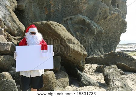 Santa Claus holds a blank white sign on the beach. Room for your text. Santa Sign. Santa Claus Sign.