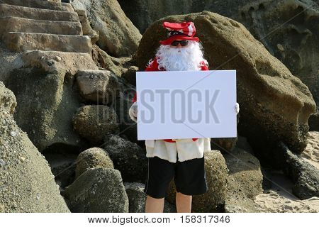 Santa Claus holds a blank white sign on the beach. Room for your text. Santa Sign. Santa Claus Sign. Blank Sign. White sign. Room for your text.