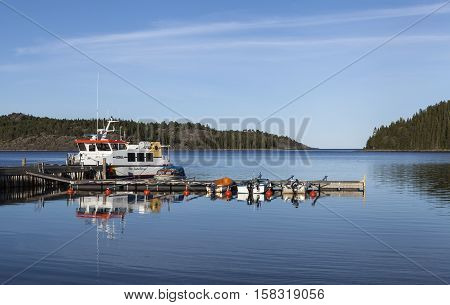 HIGH COAST HERITAGE, SWEDEN ON SEPTEMBER 05. View of the evening lit in a small harbor on September 05, 2016 in Barsta, Sweden. Bridge and boats. Dusk. Editorial use.
