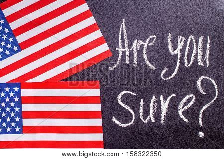 Are you sure  on the chalk board and US flag. Election concept