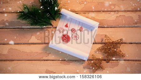 Snow falling against christmas fir, star and paper on wooden plank