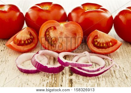 tasty ripe tomatoes with red onions on a white grainy wooden board