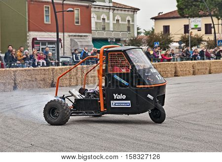 SAN PIETRO IN VINCOLI, RAVENNA, ITALY - OCTOBER 23: driver drifting on a three-wheeled Italian vehicle Ape Piaggio powered with Kawasaki GPZ engine in