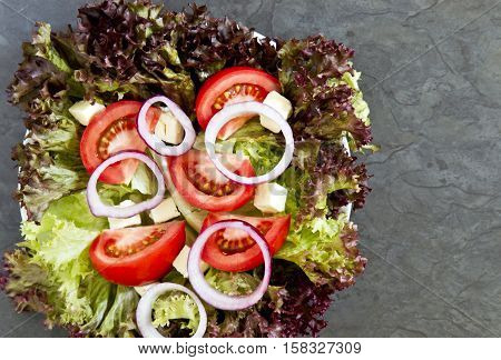 Beautiful tasty fresh salad with red onion tomato feta cheese and lettuce from above on a grey slate background