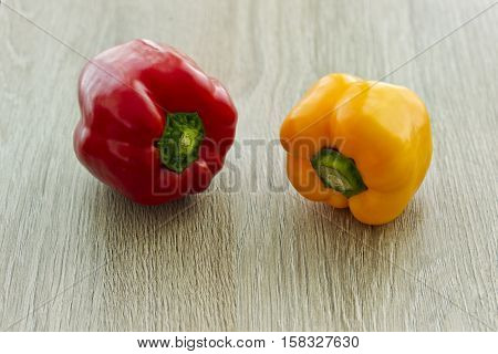 Tasty fresh red and yellow peppers on a textured wooden background