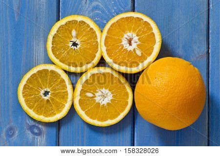 different sizes of fresh sweet sliced oranges on a old blue textured wooden background