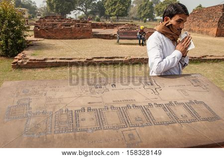 Archaeological heritage of India ruins of university of Nalanda on February 2 2014. At a stone with the scheme of excavation the Indian guide has earned reward.