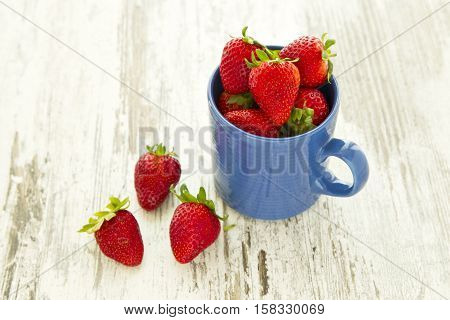 Blue mug filled to the brim with beautiful ripe red strawberries on a white wooden background