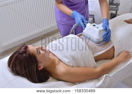 Beautiful young woman getting cryolipolyse treatment in cosmetic cabinet