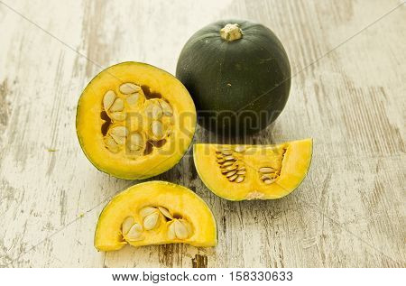yellow and green squash vegetable cut into pieces on a white wooden cutting board