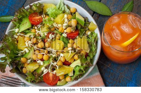 Healthy green salad with orange avocado tomatoes sprouts of mung bean citrus juice. Perfect for the detox diet or just a healthy meal. Love for a healthy raw food concept.