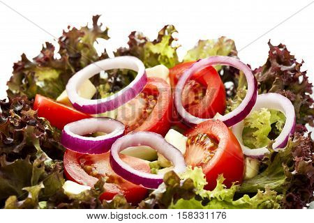 beautiful tasty fresh salad with red oniontomatoesfeta cheese and lettuce isolated on white