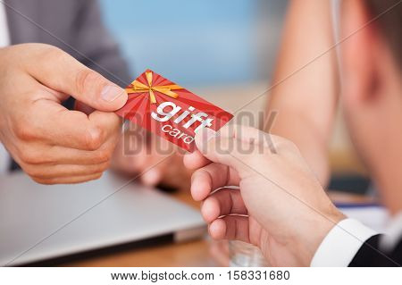Close-up Of Person Hand Giving Gift Card To Another Person