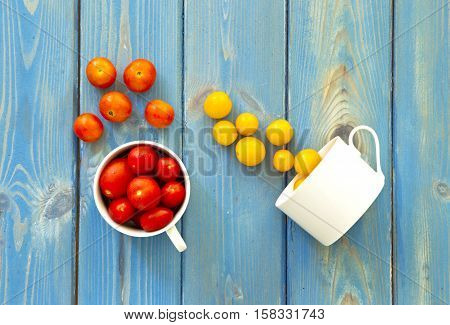 two white cups with redyellow and orange tomatoes pouring them onto a blue wooden textured background