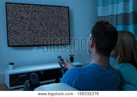 Young Couple With Remote Control Sitting In Front Of Television Showing No Signal