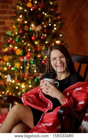 Young woman sits in a rocking-chair having wrapped up with a plaid near Christmas-tree. She holds a cup in hand. Woman with pleasure has a rest. She smiles. The Christmas tree glow electric garlands.