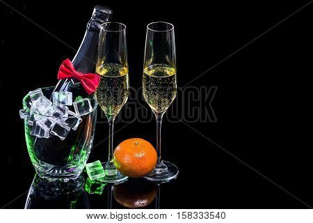 Bottle of champagne in an ice bucket and wineglasses with mandarin