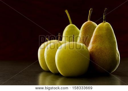 tasty fresh apples and pears in morning light on a arranged dark grey background