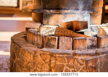 Firewoods burn in oven made of stone in traditional style