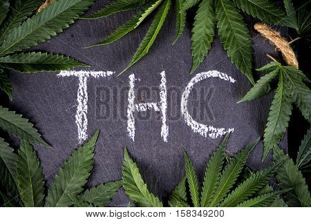 Medical marijuana background with cannabis leaves and THC hand written on dark board
