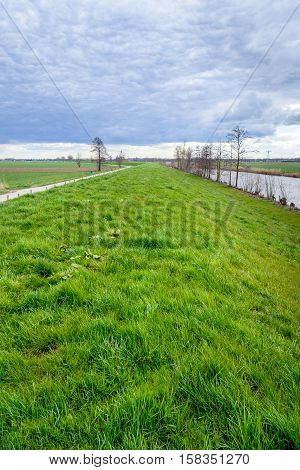 Curved embankment in a polder in the Netherlands on a cloudy day in the beginning of the spring season. Next to the dike is a canal and on the other hand a narrow country road.