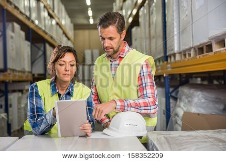 Man and a woman have short meeting in a warehouse in checking inventory levels of goods. First in first out Last in last out team working together concept photo.