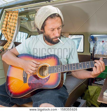 Man Playing Guitar In Camper Van