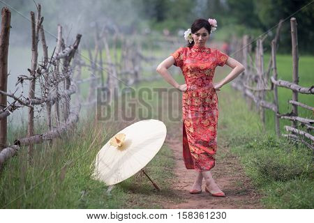 Portrait beautiful Chinese girl with dress traditional Cheongsam concept in Garden