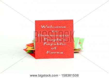 red note paper with text welcome to Democratic People's Republic of Korea