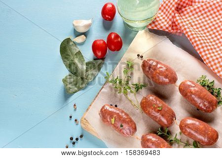 Raw chorizo sausages with bay leaves pepper and tomatoes