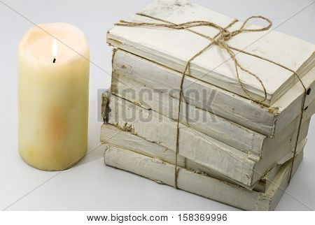 Beautiful stacked old books and a burning candle isolated on white background