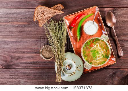 Vegetable soup broth with noodles herbs parsley and vegetables in bowl with sour cream spice pepper dried thyme and bread on dark wooden background healthy food. Top view