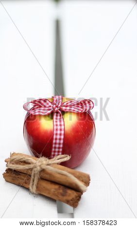 red apples and a bundle of cinnamon sticks, festive fruit and spice on w hitew wooden crate, shallow depth of field