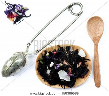 Tea Leafs Concept with Vintage Brewing Spoon Heap of Tea with Fruits and Flowers Leafs in Wooden Plate and Wooden Spoon closeup on White background