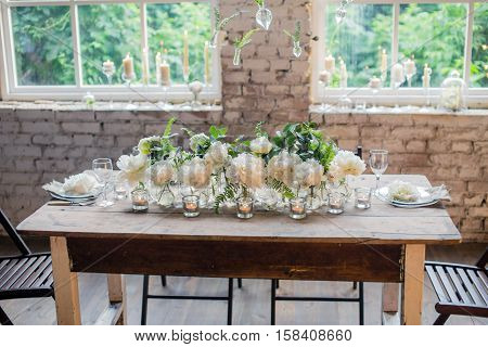 Loft style wedding table decorated with white rare David Austin roses. Beutiful rustic wedding decoration. Candles in glass holders. Nice romantic flowers.