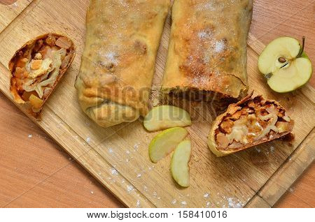 homemade cake - roll strudel. Lying on a wooden cutting board lightly sprinkled with flour. Nearby lies an apple. Space for text, Christmas food. A festive meal. next to cut a piece of strudel