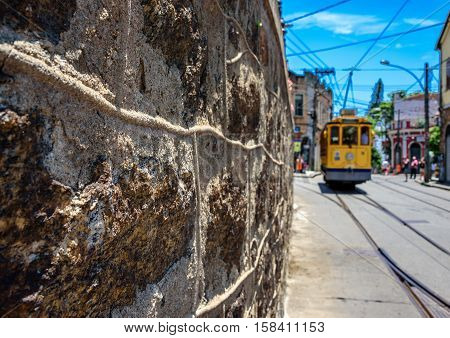 The stone wall, blue sky and old-fashioned yellow tram bonde going by tram tracks in Santa Teresa district of Rio de Janeiro, Brazil