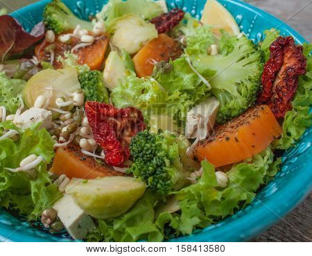 Salad with sweet potatoes dried tomatoes avocado broccoli brussels sprouts tofu mung bean sprouts. Perfect for the detox diet or just a healthy meal. Love for a healthy raw food concept.