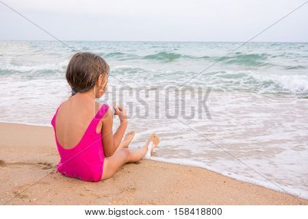 The Girl In The Pink Bathing Suit Sitting On The Beach, Eating A Wafer And Looks Into The Distance