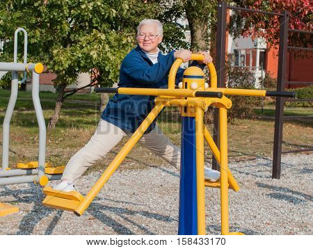 Senior woman doing exercise outdoors in park