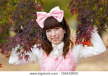 Japanese girl dressed in lolita cosplay fashion posing in Tokyo park